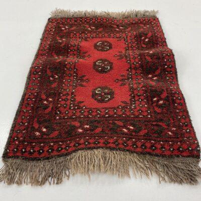 raudonas rankų darbo kilimėlis su geometriniais ornamentais