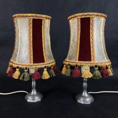 Naudoti staliniai šviestuvai alavo stovu ir raudonai baltais gaubtais su kutais