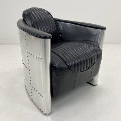 Vintage stiliaus fotelis juodos odos sėdimąja dalimi, nerūdijančio plieno lakštais apmuštu rėmu