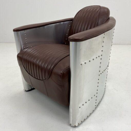 Vintage stiliaus fotelis rudos odos sėdimąja dalimi, nerūdijančio plieno lakštais apmuštu rėmu
