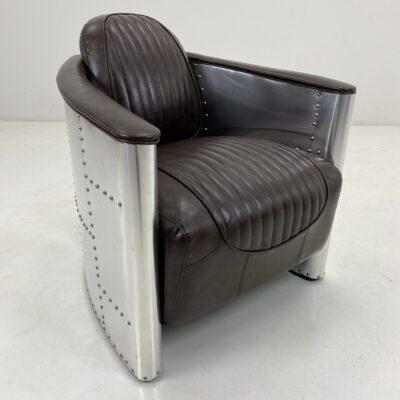 Vintage stiliaus fotelis tamsiai rudos odos sėdimąja dalimi, nerūdijančio plieno lakštais apmuštu rėmu