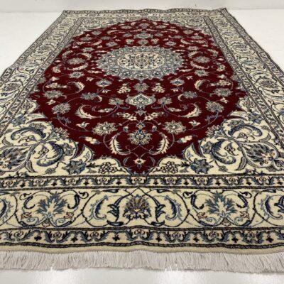 Baltas su raudonu centru ir melsvais augaliniais ornamentais dekoruotas persiškas rankų darbo kilimas Nain