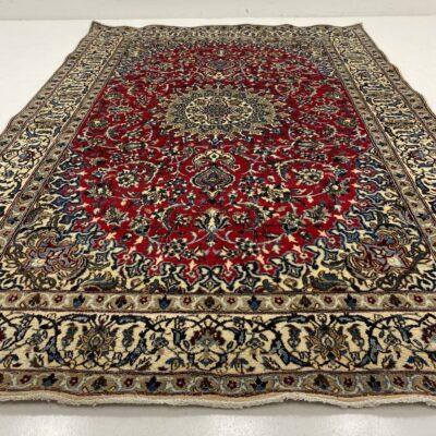 Šviesių ir raudonų atspalvių augaliniais ornamentais dekoruotas persiškas rankų darbo kilimas Nain