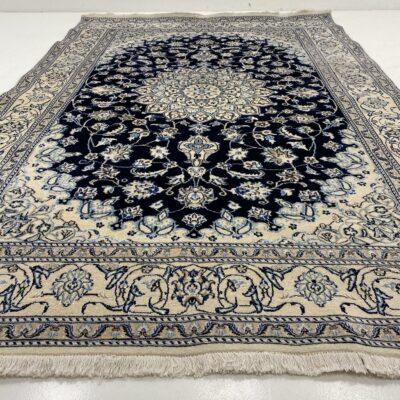 Baltas su juodu centru ir melsvais augaliniais ornamentais dekoruotas persiškas rankų darbo kilimas Nain
