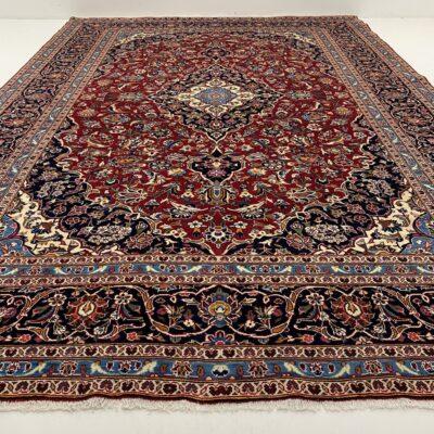 Margas augaliniais ornamentais tamsiai raudoname ir mėlyname fone dekoruotas persiškas rankų darbo kilimas Keshan