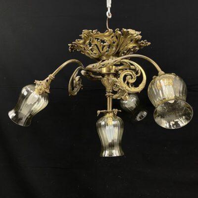 Pakabinamas šviestuvas lietos bronzos korpusu su keturiais stikliniais gaubtais.