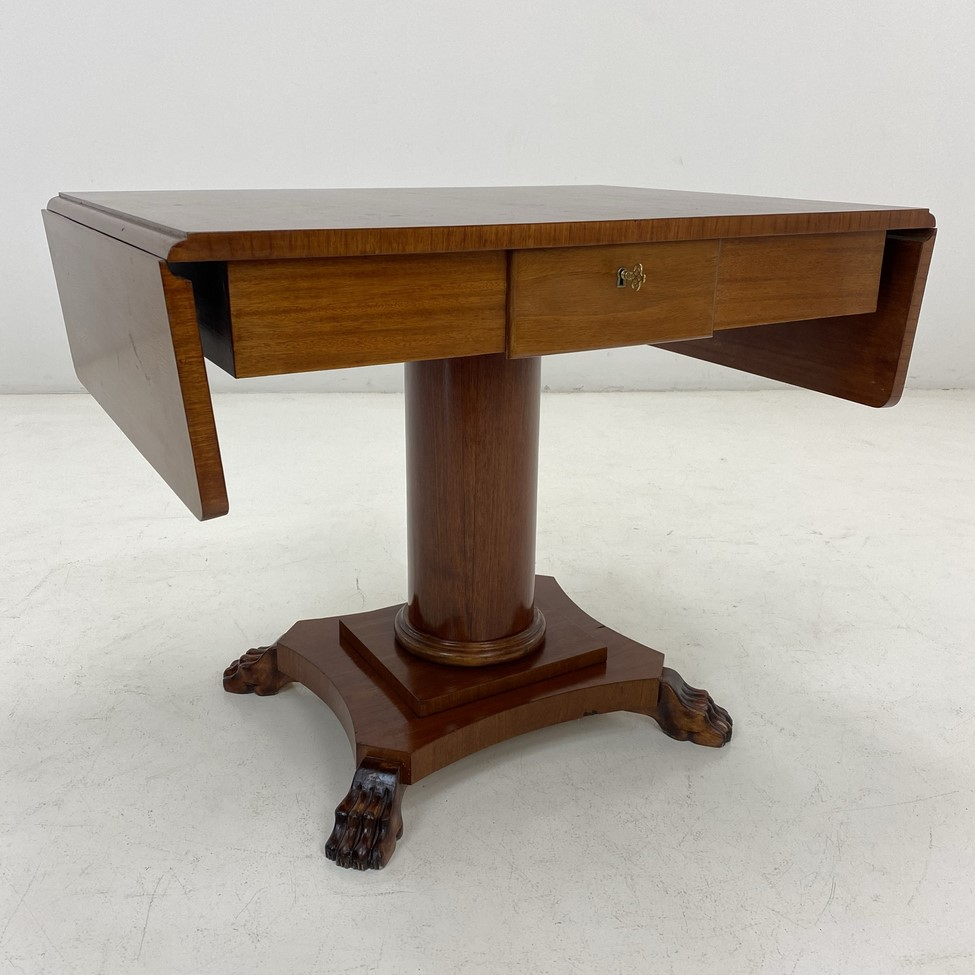 Išskleidžiamas raudonmedžio stalas atlenkiamais kraštais su stalčiumi, kolonos formos stovu su liūto letenas imituojančiomis kojomis