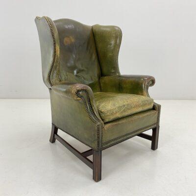 Senovinis fotelis mediniu rėmu, aptrauktas žalia oda
