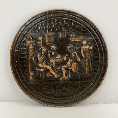 Pakabinama dekoratyvinė varinė lėkštė su reljefiniais žmonių smuklėje vaizdais