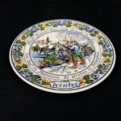 Spalvota pakabinama dekoratyvinė Delft keramikos lėkštė su žiemos darbus vaizduojančiu piešiniu