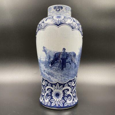 """Mėlyna olandų keramikos įmonės """"Delft"""" vaza dekoruota gėlių žiedais ir piemens ganančio karves piešiniu"""