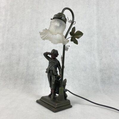 Metalinis šviestuvas su berniuko skulptūra ir gėlės žiedo formos stikliniu gaubtu
