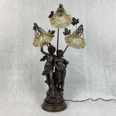 Metalinis šviestuvas su vaikino ir merginos skulptūra ir gėlės žiedo formos trimis stikliniais gaubtais