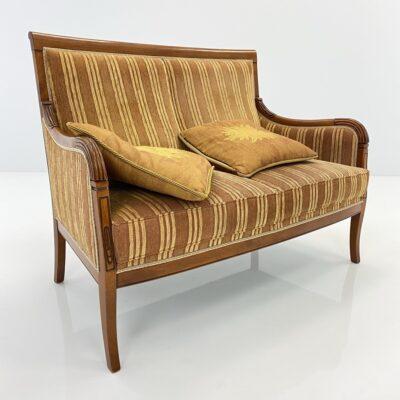 Senovinė sofa šviesiu mediniu rėmu, aptraukta gelsvos spalvos dryžuotu gobelenu