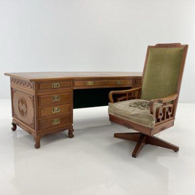 Rytietiškas palisandro rašomasis stalas dekoruotas ornamentais su spintele ir stalčiais ir krėslas aptrauktas žaliu gobelenu