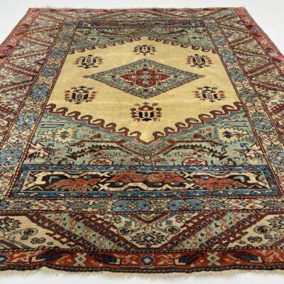 Gelsvai margas persiškas rankų darbo vilnonis kilimas dekoruotas geometriniais ornamentais