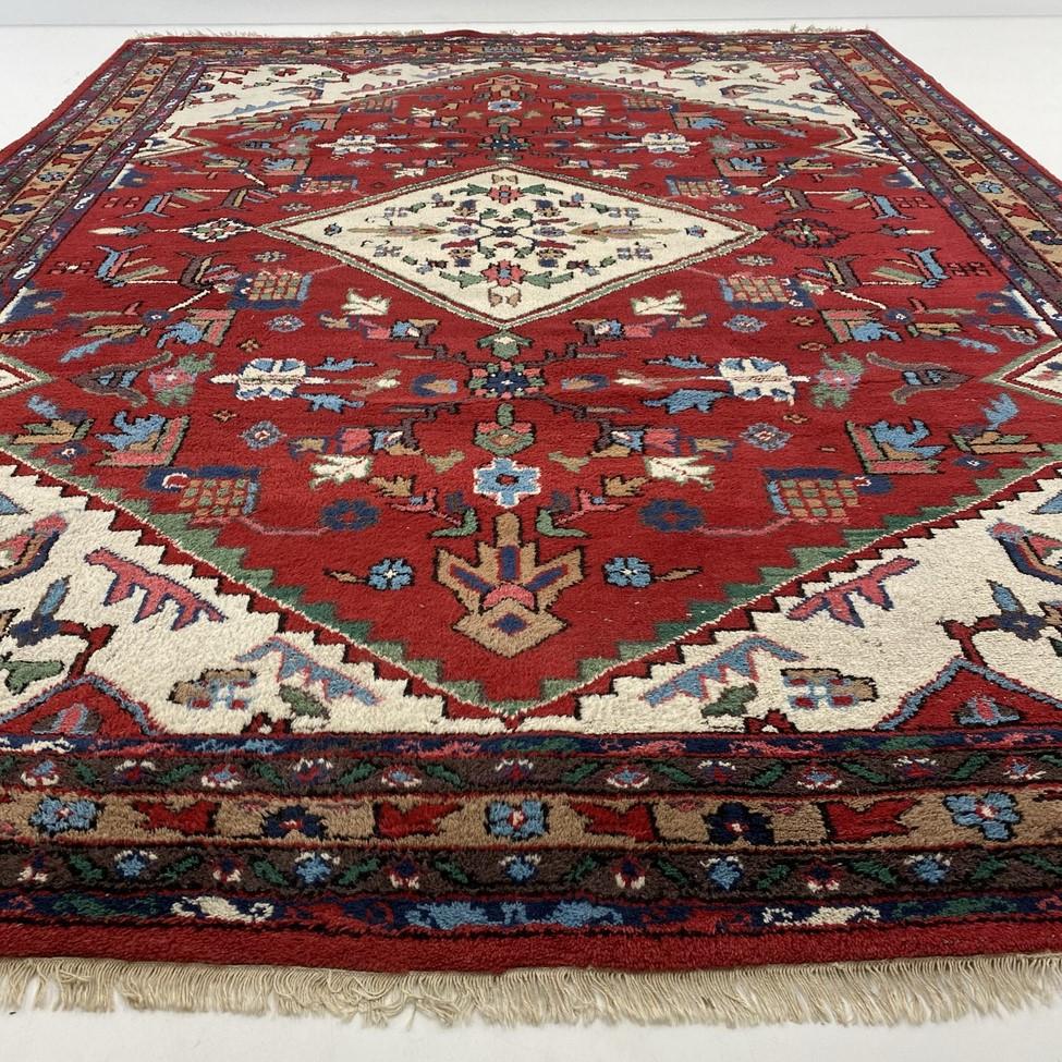 Raudonas indų rankų darbo kilimas dekoruotas geometriniais ir augaliniais ornamentais
